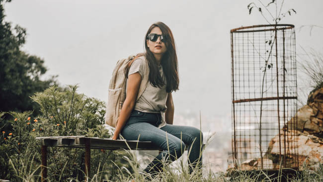 girl sitting on bench with slow fashion backpack