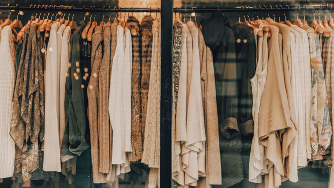 rack of clothes filled with shirts jumpers and blouses in natural colours but is it vegan fashion