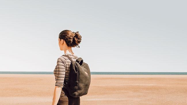 Environmentally-friendly-backback-girl-on-sand-near-the-sea