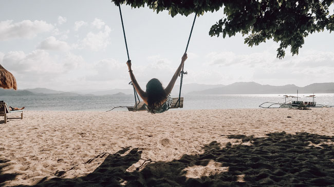 ethical banking and investing, beach girl on a rope swing