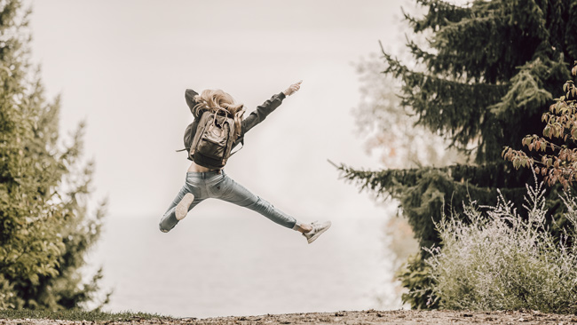 Woman jumping in the air for joy due to her eco friendly backpack