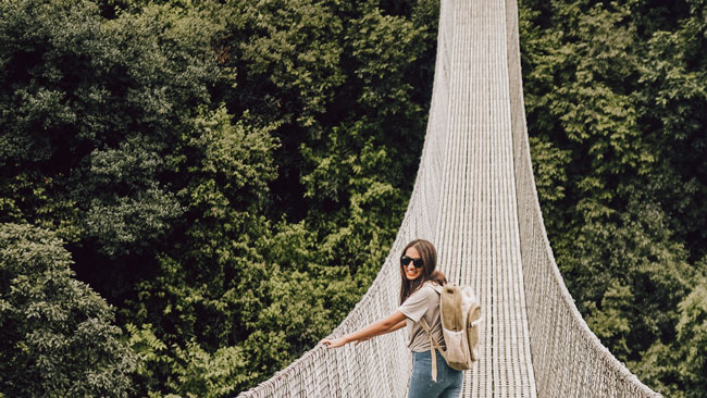 girl wearing a Bagmaya sustainable backpack on a bridge above a rainforest