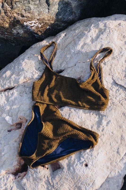 Olive green sustainable bikini by Ohoy Swimwear laid on the rocks