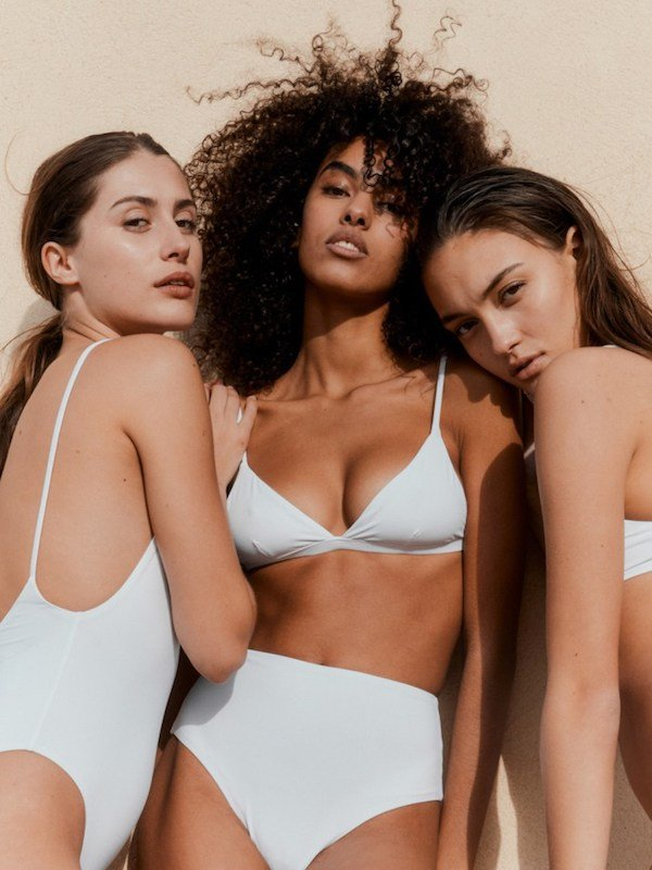 Three women from different backgrounds wearing white sustainable swimsuits by Vanessa Sposi