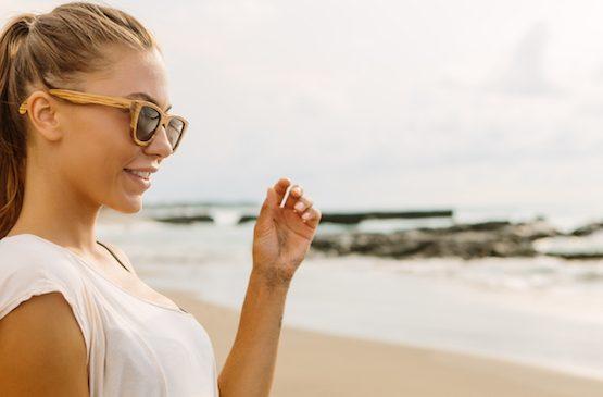 Beautiful girl wearing bamboo sunglasses by the beach