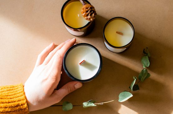 Woman's hands holding the eco-friendly candles with wooden and cotton wicks.