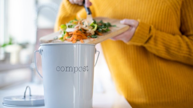Close up of woman making indoor compost from leftover vegetables