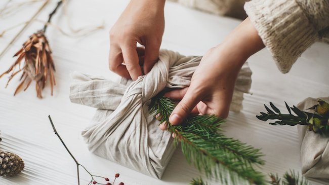 Hands decorating sustainable christmas gift in linen fabric with green fir branch.