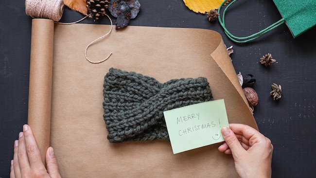 Flat lay of a handmade knitted headband being wrapped in brown paper as a sustainable Christmas gift